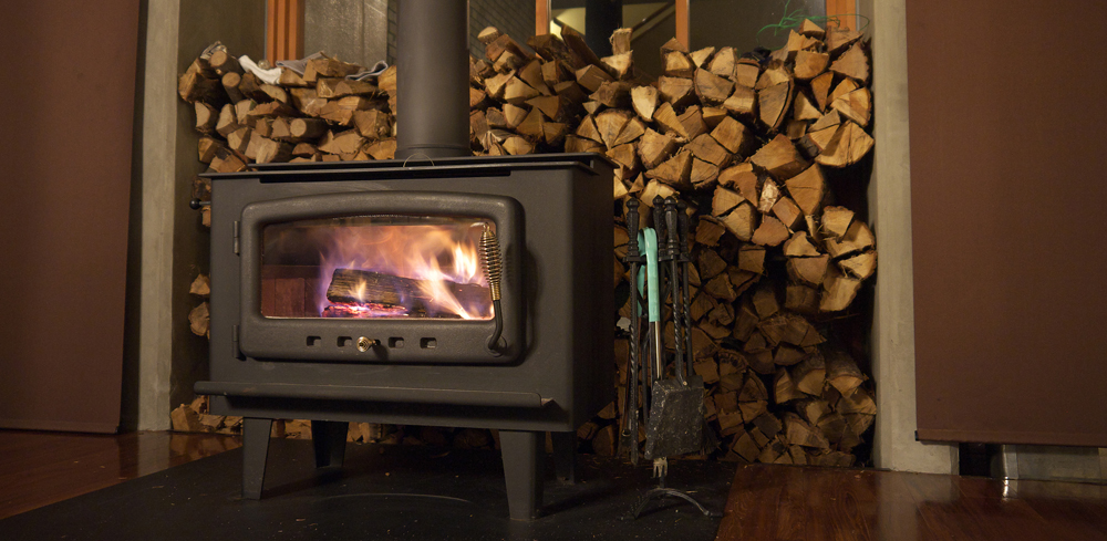Burning wood stove with with pile of firewood